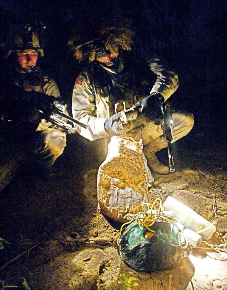 Soldiers of the U.S. Army's 4th Infantry Division inspect an improvised explosive device from a weapons cache discovered during a raid against a suspected Fedayeen organization in Tikrit, Iraq, on Thursday.