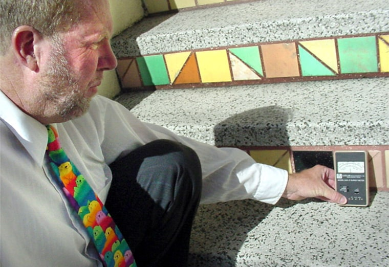 Radiation watchdog Walter Wagner holds his Geiger counter against riser tiles at a San Francisco apartment building.