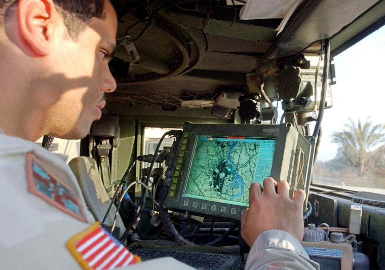 U.S. Army Spc. Michael Scott, from Michigan, of the 1st Battalion 22nd Regiment 4th infantry division, sitting inside his humvee checks a map on a computer screen, in Tikrit, Iraq, Wednesday, Dec. 31, 2003.