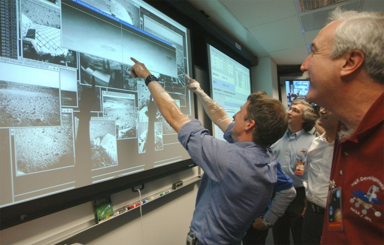 NASA Administrator Sean O'Keefe, right, and Principal Investigator Steve Squyres, pointing at screen, examine the first images arriving from Mars after the landing of the Spirit roveron Saturday night.