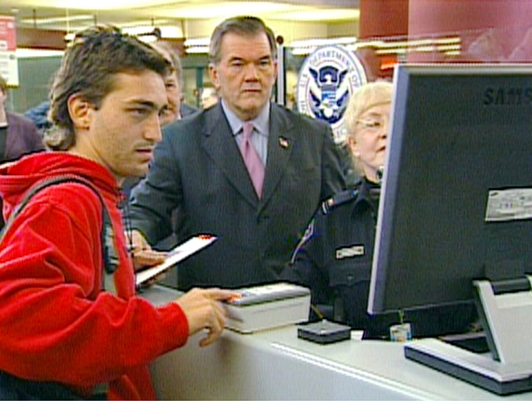 Secretary of Homeland Security Tom Ridge watches as a foreign visitorgets fingerprinted and photographedat a US-VISIT station at Atlanta'sairport.