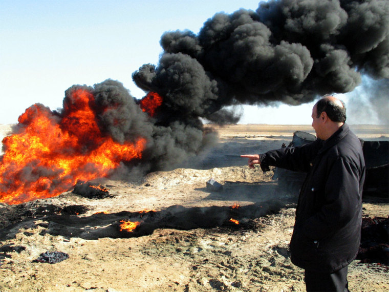 An Iraqi official of the Ministry of Oil looks at a burning pipeline last month near Samarra, 75 miles north of Baghdad. Thieves trying to steal gasoline caused an explosion when they breached a pipeline creating a blaze that burned out three cars that were loaded with barrels of gas.