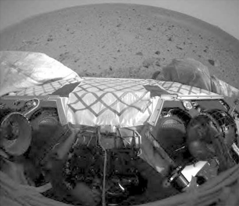 """This wide-angle image from the Spirit rover's front hazard avoidance camera shows the rover's wheels after a """"stand-up"""" procedure, completed in preparation for rolling off the landing platform next week. The two wheels on the bottom right and left are locked into position, along with the suspension system. The Martian landscape lies beyond."""