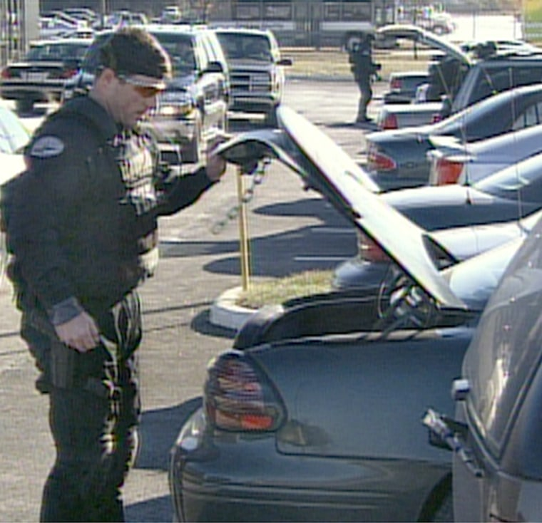 A police officer searches the trunk of a car aprked at Dulles airport after a plane was diverted there.
