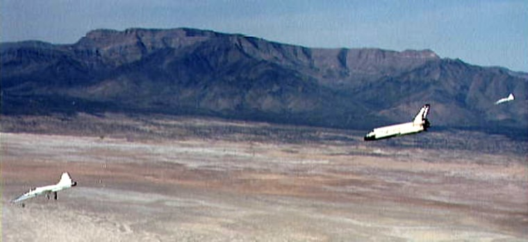 Escorted by chase planes, the space shuttle Columbia glides down toward a landing at the White Sands Space Harbor in New Mexico in March 1982 — the only time a shuttle has landed at the facility.