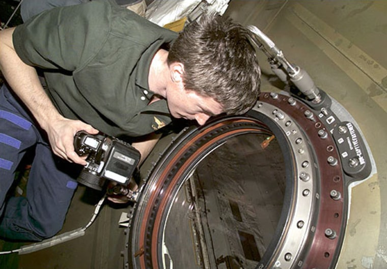 "In a February 2001 photo, space station astronaut Sergei Krikalev peers out the Destiny module's optical-quality window. The U-shaped ""flex hose"" is visible above his head."