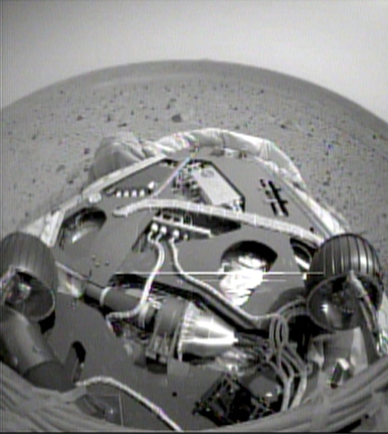 A fisheye view from one of the Spirit rover's navigation cameras shows the rover's front wheels, the front of its landing platform and the Martian landscape beyond. This shot was taken after Spirit backed up and executed a 45-degree turn on the platform.