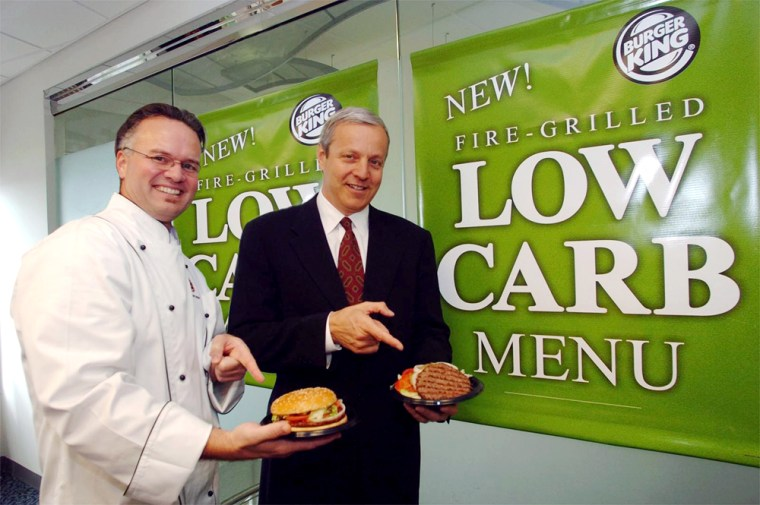 """David """"Guilley"""" Guilfoyle, left, manager of product development for Burger King Corporation holds the original Burger King Whopper, while Brad Blum, CEO of Burger King, touts the new Low-Carb Whopper."""