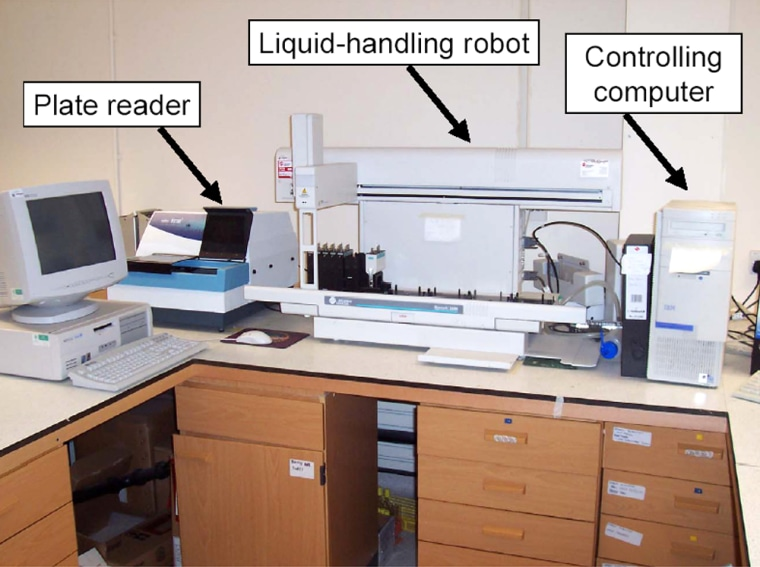 The robotic researcher looks like a desktop's worth of computer-gray equipment. This labeled photo points out the components of the system that studied yeast genetics.
