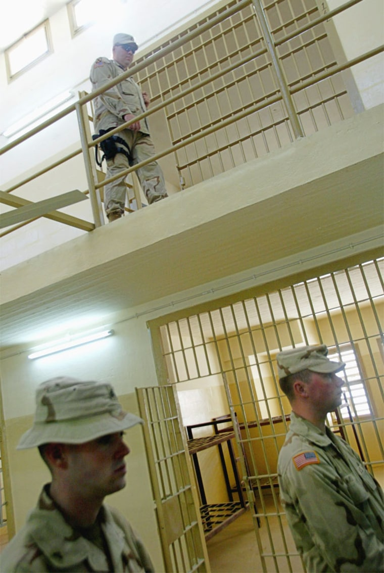 U.S. soldiers walked past prison cells at the Abu Ghraib prison just outside Baghdad in September.
