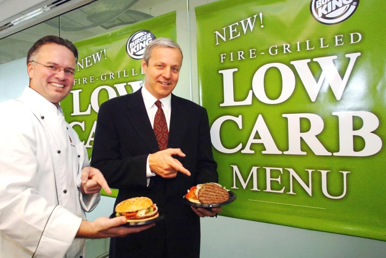 David Guilfoyle, left, manager of product development for Burger King Corp., holds the original Burger King Whopper, while Brad Blum, CEO of Burger King, holds the new low-carb Whopper. The bunless sandwiches became available nationwide on Jan. 13.