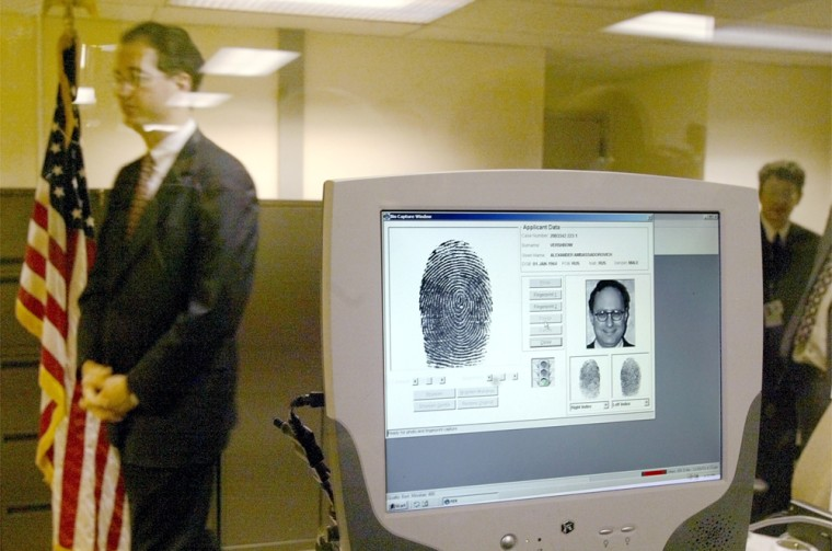 A U.S. embassy official walks past a monitor displaying biometric data during a demonstration of a new procedure, fingerprint scans, to the media at the U.S. Embassy in Moscow late last year.