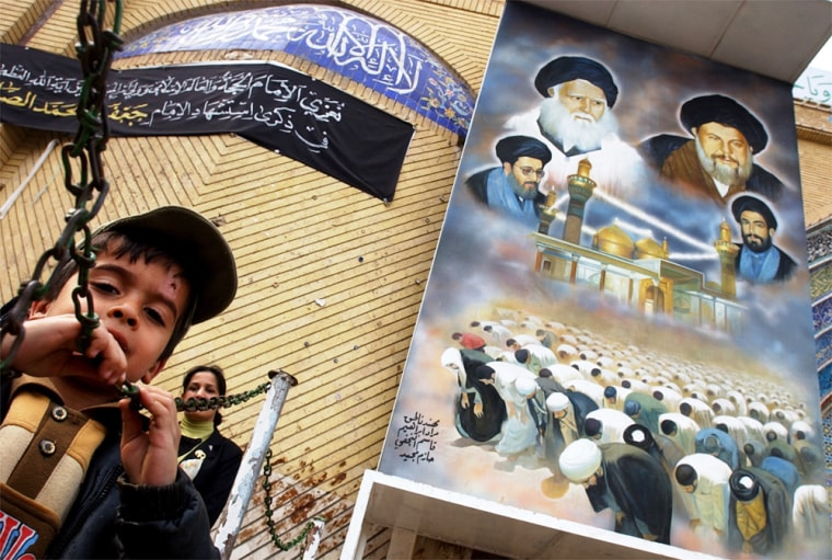 An Iraqi Shiite muslim boy and his mother exit the Kadimiyah shrine beneath a giant mural of important Iraqi Shiite clerics in Baghdad.