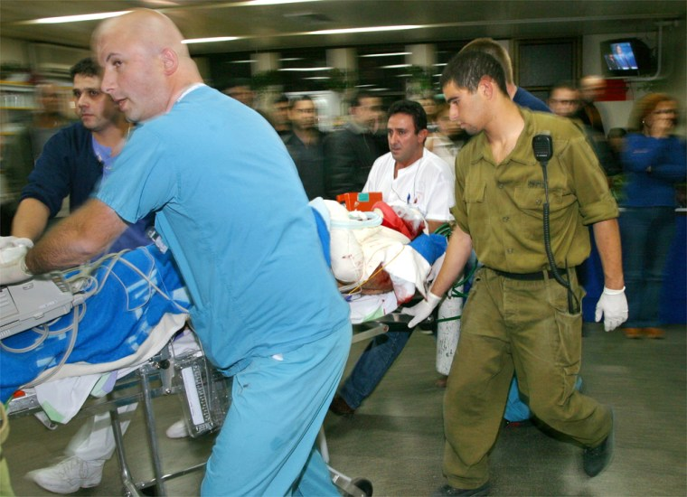 An Israeli soldier, who as seriously wounded when his bulldozer was hit by an anti-tank missile on the border with Lebanon on Monday is rushed out ofa hospital in the northern Israeli town of Nahariya to be transferred by helicopter toa hospital in Haifa.