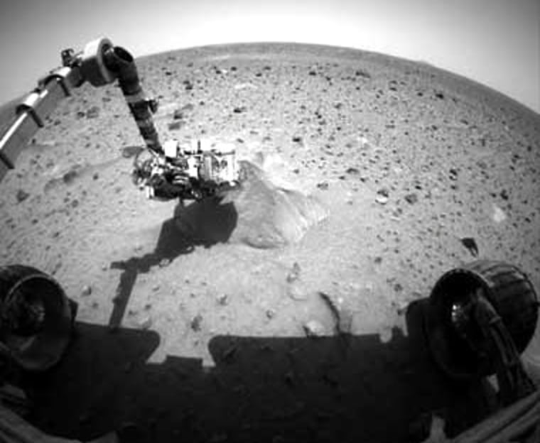 At the time this picture of Spirit probing its first target rockwas snapped, the rover was analyzingit with its alpha particle X-ray spectrometer.
