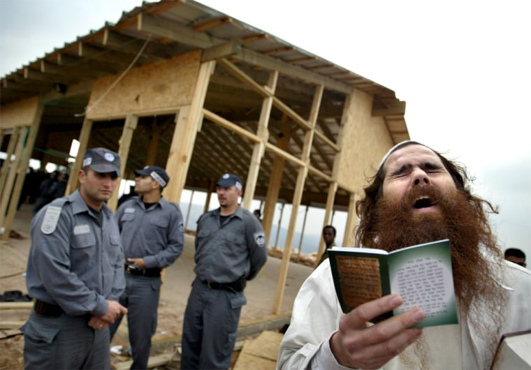A supporter of the right-wing Jewish settler movement prays Tuesday as Israeli policemen stand before dismantling an unfinished synagogue, background, in the West Bank settlement outpost of West Tapuah.