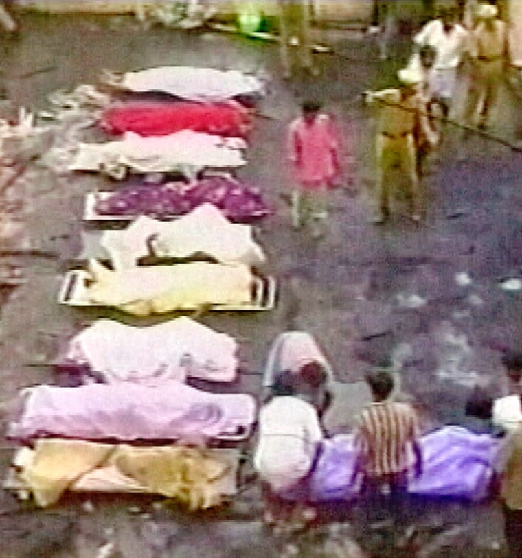 RESCUE WORKERS STAND NEAR VICTIMS OF FIRE AT A WEDDING IN SOUTHERN INDIA