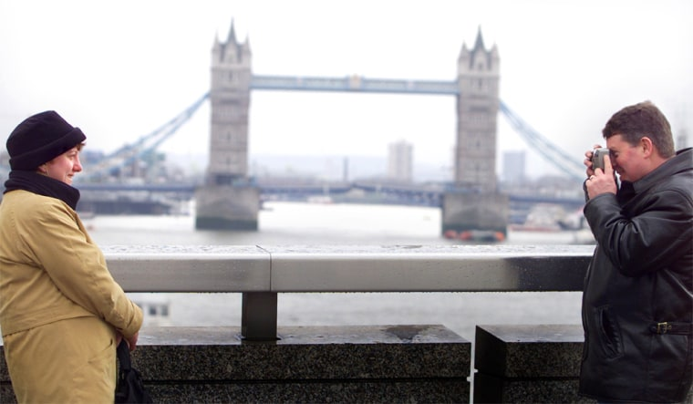 TOURISTS TAKE PHOTOGRAPHS OF EACH OTHER IN FRONT OF LONDONS TOWER BRIDGE