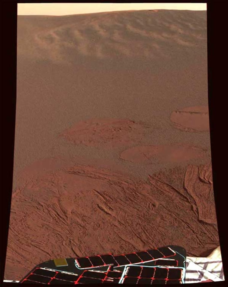 The first color snapshot sent by the Opportunity rover shows fine red-gray soil, with lighter circular tracks and drag marks left behind by the rover's airbags. Hummocky terrain stretches out toward the horizon, and portions of the rover's solar panels can be seen in the foreground.