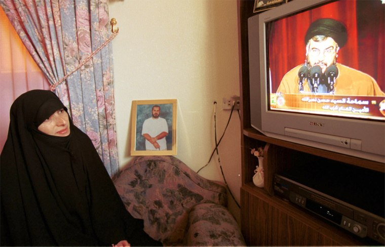 Fadila Qasfi, wife of Lebanese prisoner Jawad Qasfi, who has beenheld in Israel for 13 years, watches a televised news conference by the leader of Lebanon's militant Hezbollah group Sheik Hassan Nasrallah in her house in the southern Lebanese village of Sultaniyah on Sunday.
