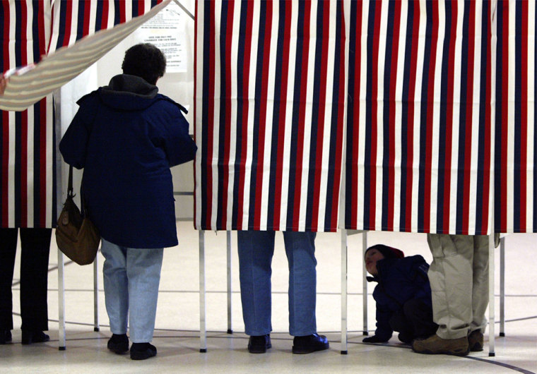 2-year-old Colin McQuinlan,right, peeks at voters in a neighboring booth at the polling station of Jewett Street School in Manchester, N. H.