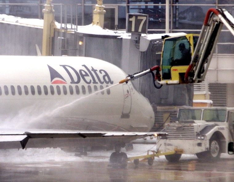 DELTA JET IS SPRAYED WITH CHEMICAL SOLUTION TO REMOVE ICE AT NATIONAL AIRPORT IN WASHINGTON