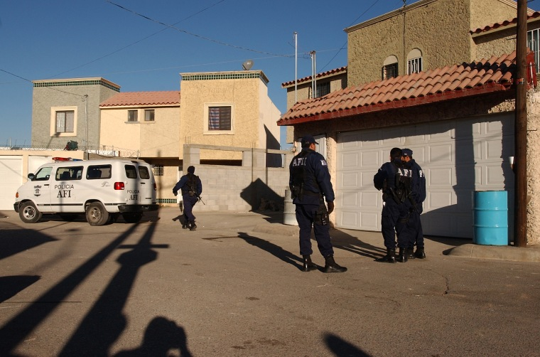 Mexican Federal Police stand guard Wednesday outside an alleged drug traffickers' safehouse. Policefound11 corpsesin the back yard.