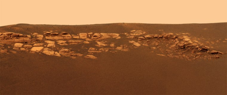 A color picture from the panoramic camera on the Opportunity rover shows bedrock outcroppings sticking up as much as a foot and half from darker material within the crater where the rover rests.