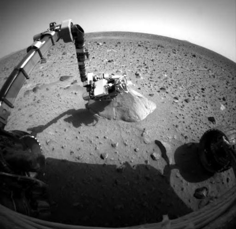 This image from the Spirit rover's front hazard identification camera, transmitted Wednesday,shows the robotic arm extended to the rock called Adirondack. Click on the image to see the identical view from a week earlier.