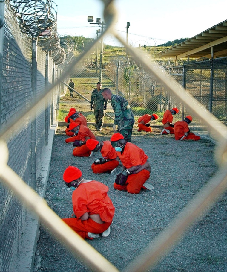 Muslim prisoners in orange jumpsuits sat in a holding area under the watchful eyes of military police at Camp X-Ray in January 2002.