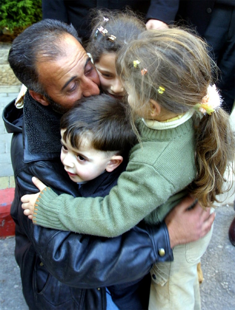 A RELEASED PALESTINIAN PRISONER HUGS HIS THREE CHILDREN AFTER HE WAS RELEASED IN THE WEST BANK