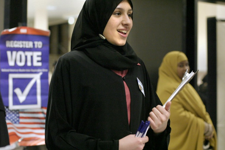 CAIR volunteer Asma Mohamed greets attendees to Eid prayer services in Seattle, Sunday.