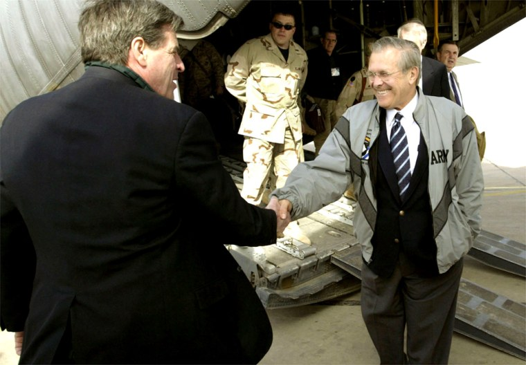 U.S. Defense Secretary Donald Rumsfeld, right, is greeted off a C-130 transport plane by U.S. administrator Paul Bremer in Baghdad on Monday.