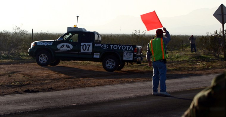 A driverless Toyota Tundra pickup, fielded by Digital Auto Drive, accelerates into the desert Saturday after crossing a highway near the starting line for the DARPA Grand Challenge.
