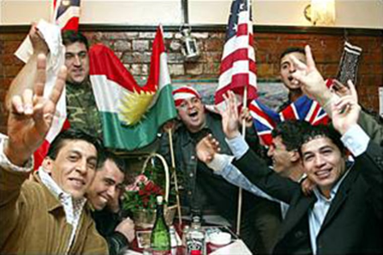 Members of the Kurdish community celebrate in the Tara restaurant in North London last month after the northern city of Kirkuk was captured by coalition forces.