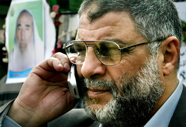Abdel Aziz Rantisi talks on a cell phone Tuesday while taking part in the mourning procession in Gaza City for slain Hamasleader Sheik Ahmed Yassin, seenin the poster.