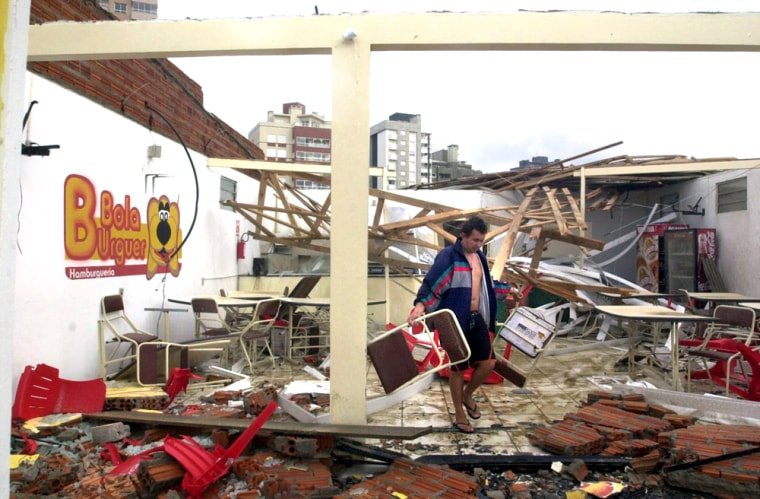 A man picks up furniture inside the remains of what used to be a snack bar in Torres, Brazil, Sunday, after a powerful storm lashed the nation's southern coast.