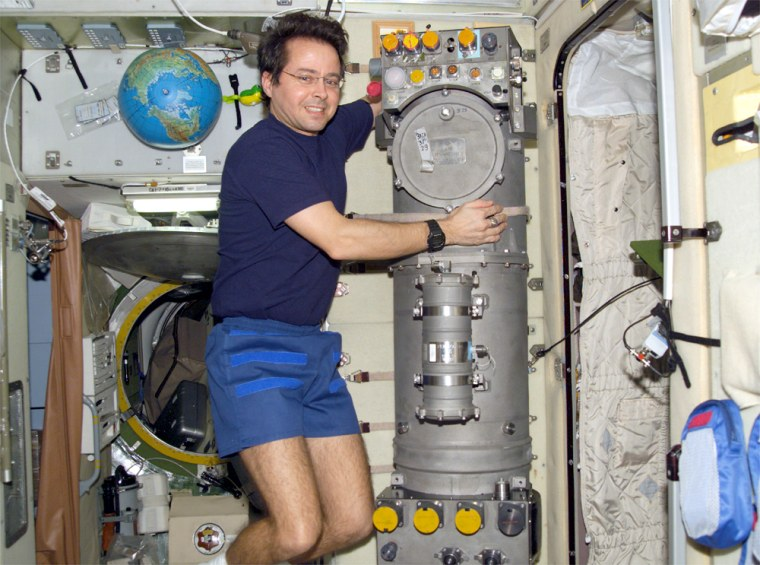 The Elektron oxygen generator aboard the international space station is seen in this photo from April 2002, with NASA astronaut Daniel Bursch floating alongside.