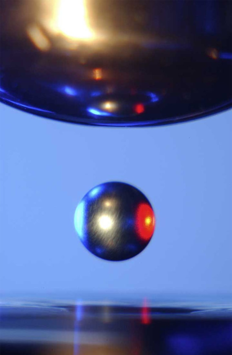 Spherical samples float in midair within the Electrostatic Levitator, thanks to static electricity generated by six electrodes. A laser beam heats the sample until it melts into a tiny levitating ball.