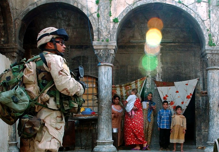 Iraqis look out from their home as a U.S. Army soldier patrols a street in Mosul onFriday.