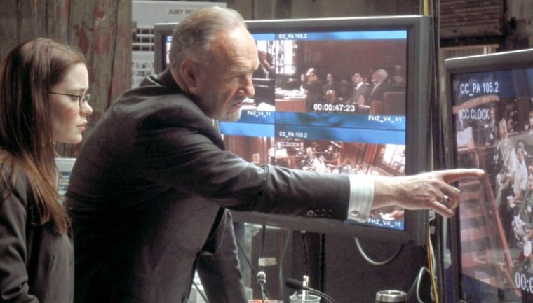 From the movie 'Runaway Jury': Jury consultant Rankin Fitch (Gene Hackman) directs operations at a high-tech command center, as his assistant, Amanda (Marguerite Moreau), looks on.