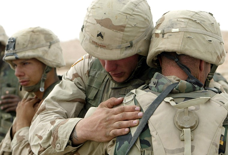 US SOLDIERS PRAY AFTER A MEMORIAL SERVICE FOR TWO FALLEN COMRADES