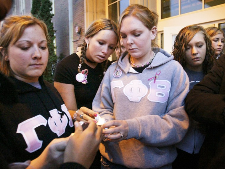 Dru Sjodin's Gamma Phi Beta sisters gather Sunday night for acandlelight vigil at the University of North Dakota in Grand Forks after a memorial service for the slain student.