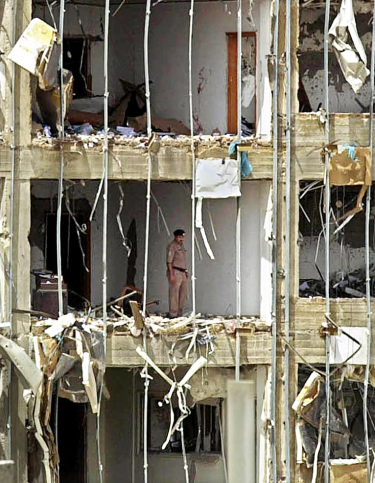 A Saudi police officer stands in the severely damaged headquarters building of the general security services Thursdayin Riyadh.