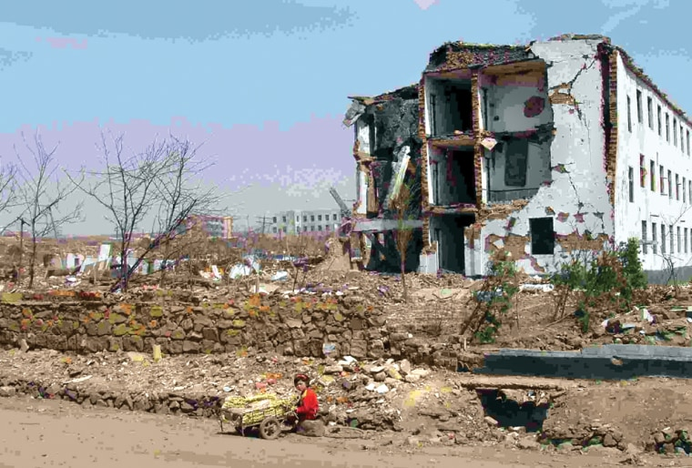 NORTH KOREAN WOMAN SITS IN FRONT OF RUINED BUILDING AFTER EXPLOSION IN RYONGCHON