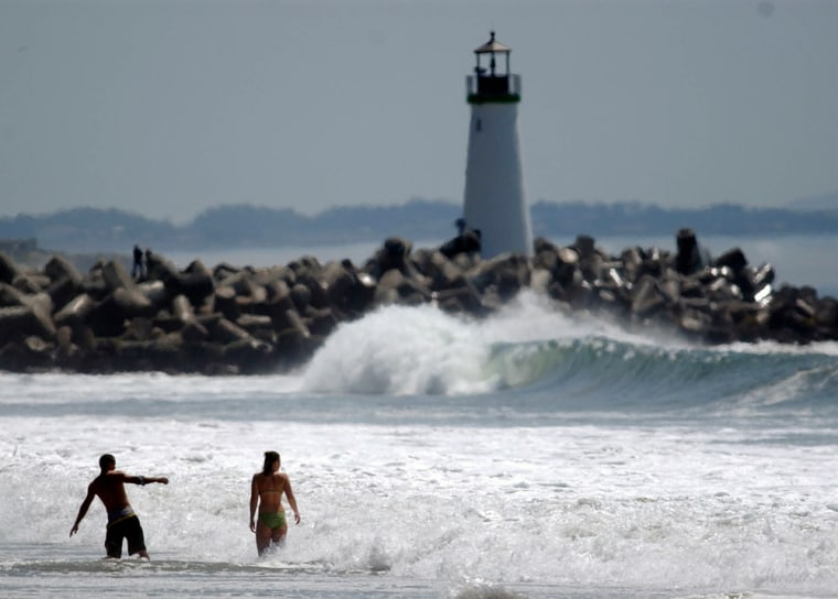 People cool offin the surf at Seabright State Beach on a sunny, warm afternoon in Santa Cruz, Calif., on Monday.