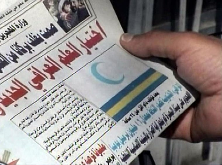 An Iraqi newspaper showed the nation's new flag on its cover Monday. The crescent represents Islam.