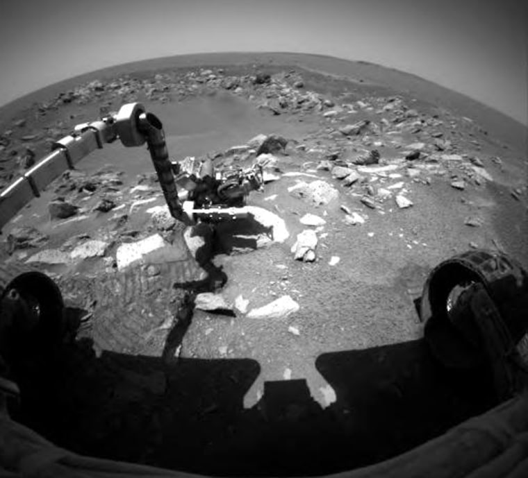 Opportunity's robotic arm reaches out to analyze a rock during Sol 87 of its mission on Mars. The rover has now completedthe initial 90-day phase of its sojourn.