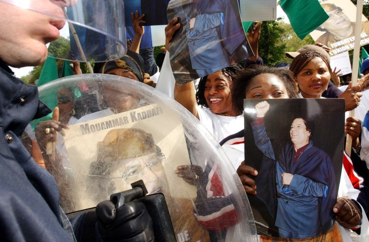 Supporters of Moammar Gadhafi show photos and posters of the Libyan leader outside European Union Commission headquarters in Brussels Tuesday.