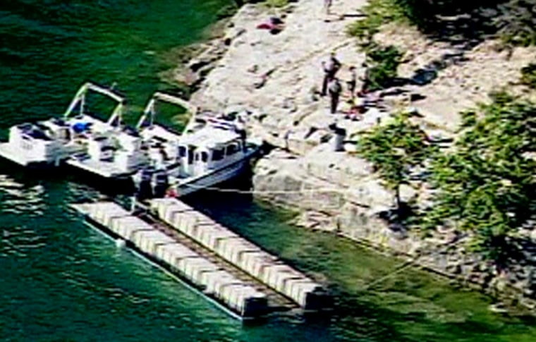 Rescue vessels near the shore of Lake Travis beside the overturned barge.